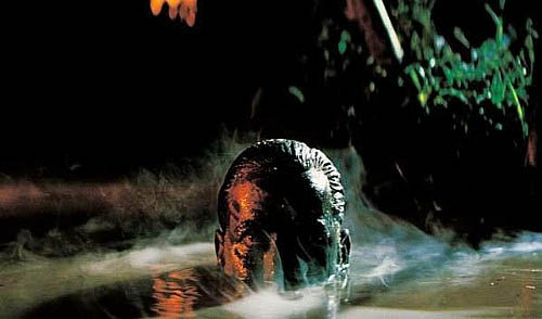 "Still from ""Apocalypse Now"" showing Captain Willard with camouflaged face rising from swampy water"